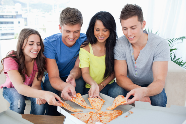 Smiling friends taking some pizza as they look at the box of pizza