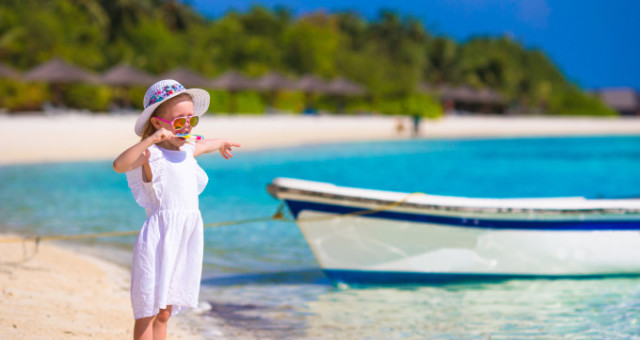 Cute little girl in hat at beach during summer vacation