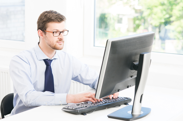 Young and confident businessman working in a modern office. Business man using computer.