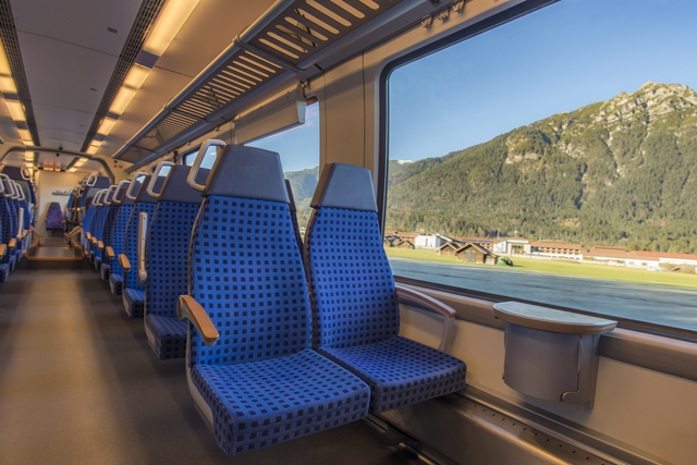 Comfortable chairs on a modern german train, with beautiful alpine view through the window