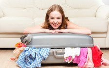 happy woman is packing a suitcase at home