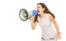 Angry young woman shouting thought megaphone