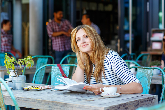Woman drinking coffee and reading book in cafe