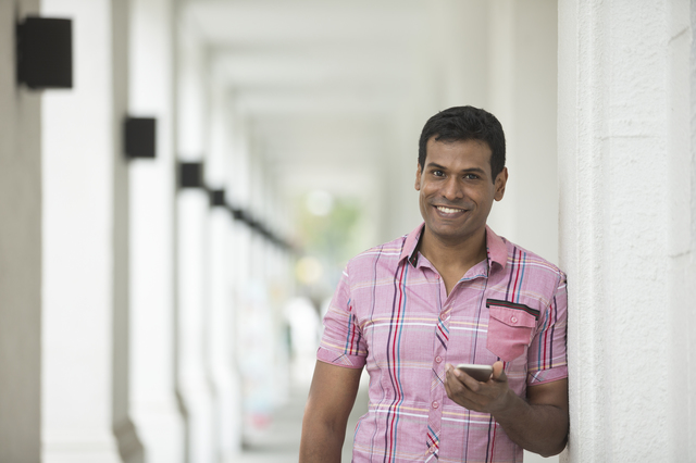 Indian man using a smart phone outdoors.