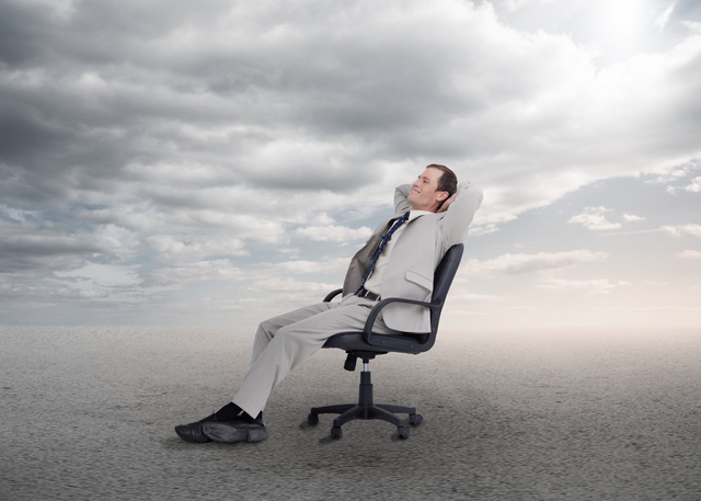 Relaxed businessman sitting on a chair in open desert setting