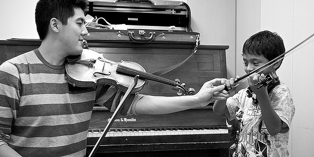バイオリンを教える男性教師