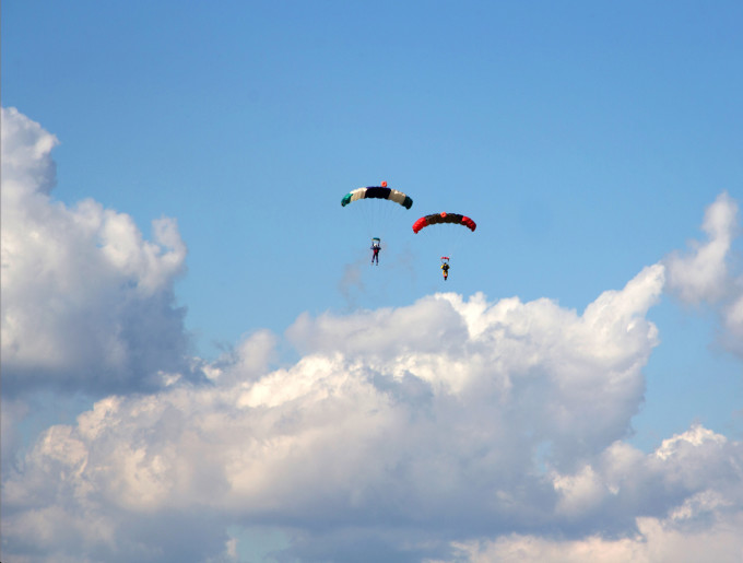 Skydivers in blue cloudy sky background