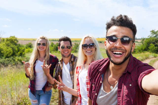 Man hold smart phone camera taking selfie photo friends face smile close up countryside young people group outdoor two couple summer sunny day