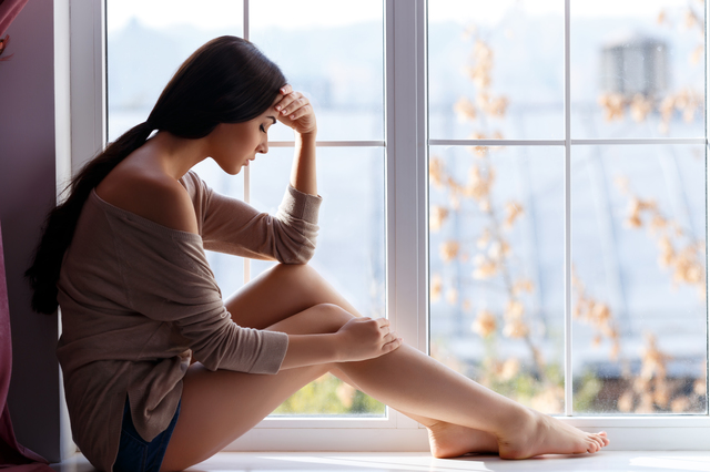 若い女の人が窓際に座って落ち込んでいる