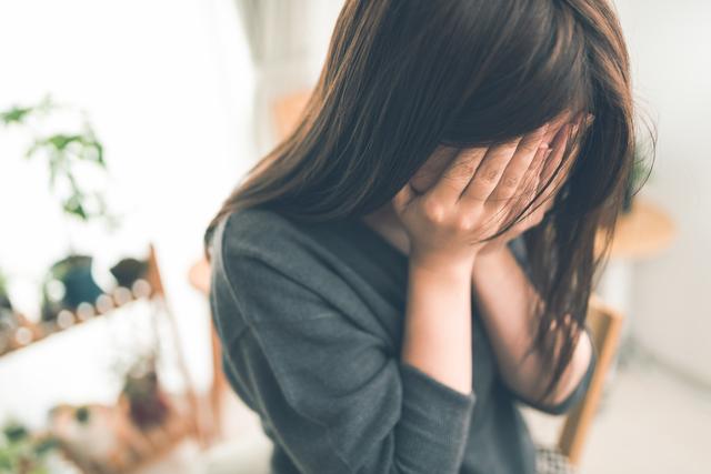 顔を隠して悲しんでいる女性
