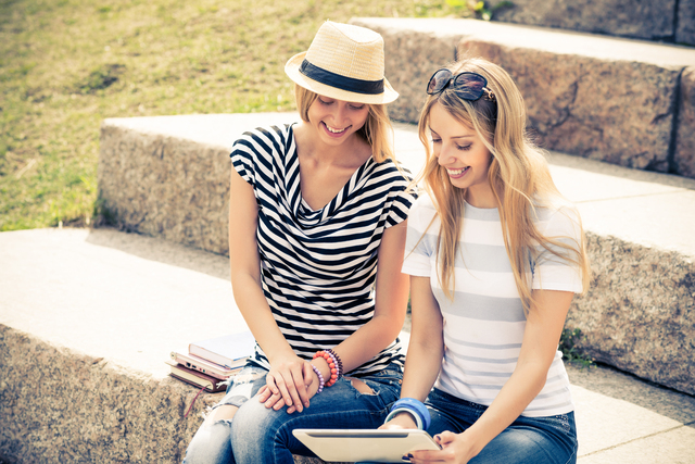 Two young female friends sitting on steps and using tablet pc
