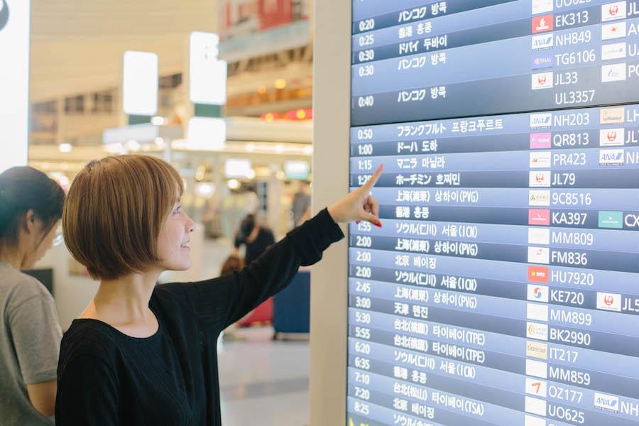 出国ボードを指差す女性