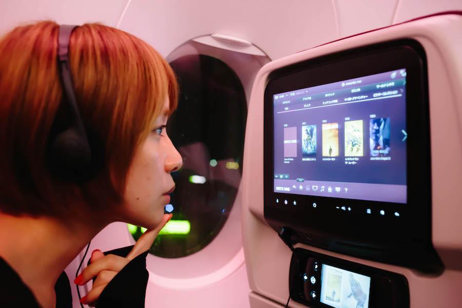 カタール航空のエンターテイメントを選ぶ女性