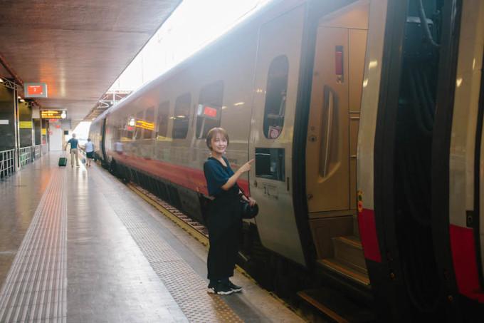 ヨーロッパの電車の前で写真を撮る女性