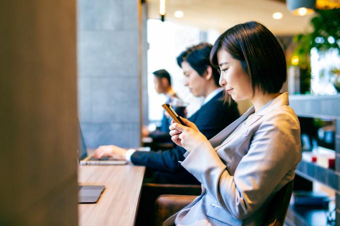 カフェで携帯をいじる女性