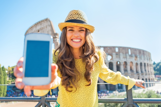 Happy young woman showing cell phone in front of colosseum in rome, italy