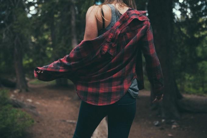 森の中でシャツを着る女性