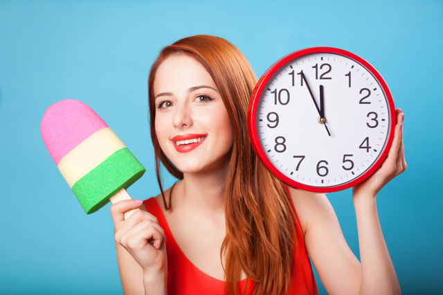 Redhead girl with toy ice cream and huge clock on blue background.