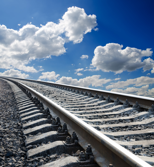 low view to railroad under deep blue cloudy sky