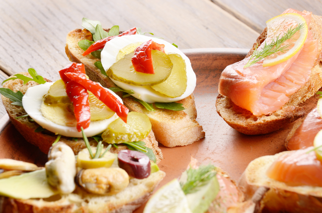 Open sandwiches with salmon, eggs and mussels on ceramic plate